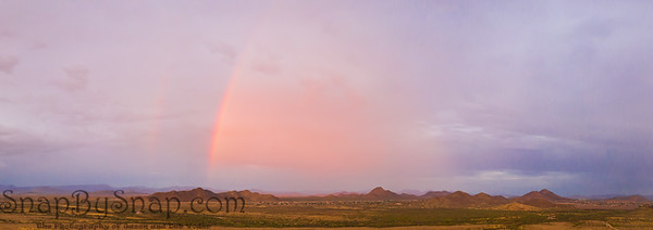 A panorama of an Arizona monsoon with a rainbow