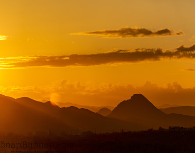 A Panorama of the sun setting behind mountains in the Sonoran Desert