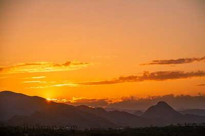 The sun setting behind mountains in the Sonoran Desert