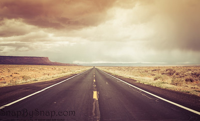 A straight road to the distant horizon across the desert of northern Arizona with the Vermillion Cliffs National Monument in the distance