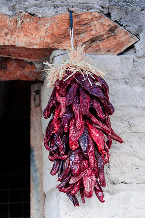 Chili peppers hanging from old building.