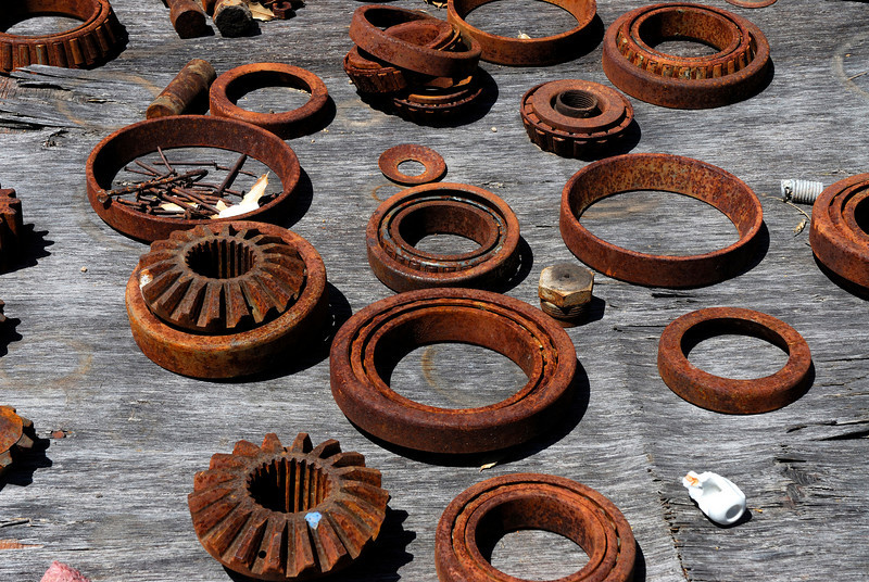 Gears and bearings found at ghost town laid out on wood table.