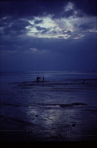 Mother and daughter on sandbar at dusk, finding shellfish