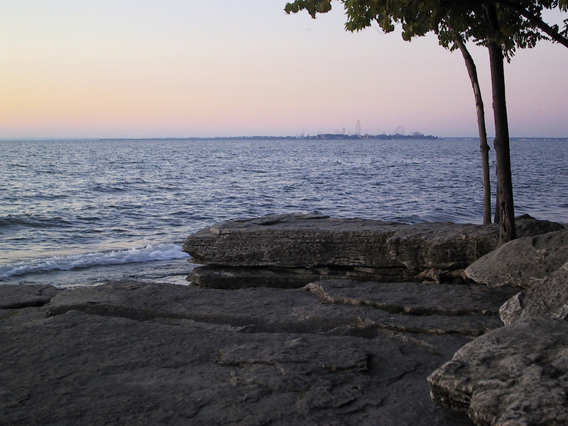 The rocky shore at Marblehead Lighthouse State Park at dawn, with Cedar Point in the distance.