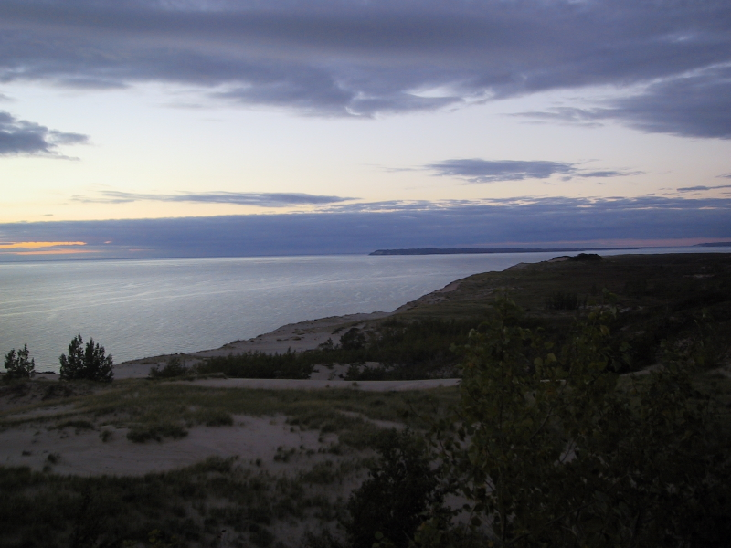 "The slight bump with darker grass, towards the right of this picture, is the top of the ""Sleeping Bear Dune"" for which the park is named.  (Here is the <a href=""http://www.nps.gov/slbe/legend.htm"">Ojibwa legend</a> which gives the dune its name.)  It was more impressive a few hundred years ago, but dunes are built up and torn down relatively quickly by erosion.  Older pictures of the dune, along with a slightly different version of the legend, can be found <a href=""http://www.geo.msu.edu/geo333/bearlegend.html"">here</a>.  In the distance are the Manitou Islands."