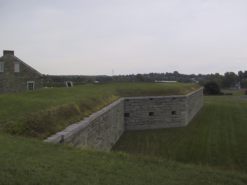 Fort wall seen from the top of the earthworks behind the wall. The outside of the embrasures can be seen.