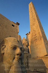 The entrance to the Temple of Luxor against a solid blue sky features Sphinx and Obelisk in Luxor, Egypt