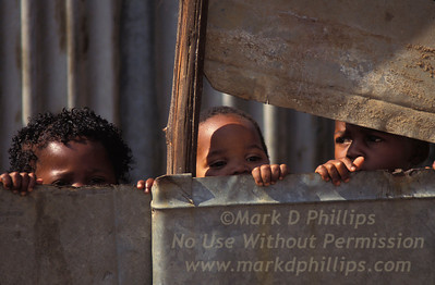 Children in Soweto, South Africa, hide behind a tin wall at their house.