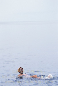 Floating on the surface of the Dead Sea with mud on her face in Israel.