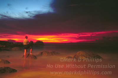 Mark D Phillips stands on rock on beach in Phuket, Thailand