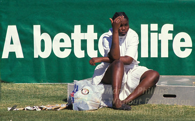 """A young woman sits in the sun at an election rally in Soweto, South Africa, with a sign stating hope for """"A Better Life"""" during Nelson Mandela's campaign to become the first African president in the troubled country in 1994."""