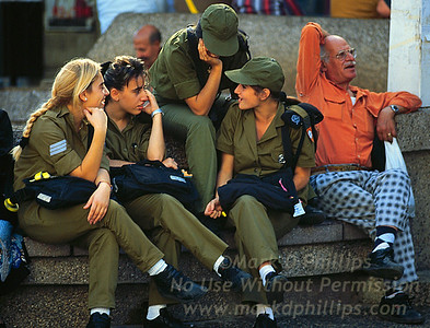 Female soldiers sit together with an elderly gentleman in Tel Aviv, Israel