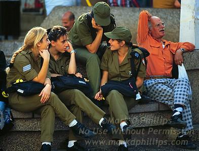 Female soldiers sit together with an elderly gentleman in Tel Aviv, Israel