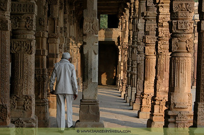 Old man passing along the columns of Qutb Minar, India