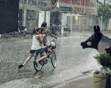 3 Girls on one bike laugh during a torrential downpour in Vietnam