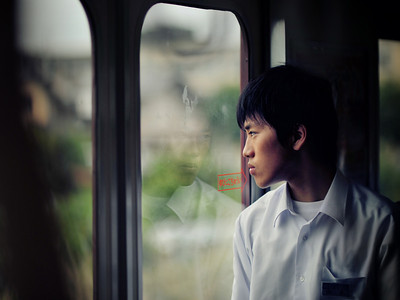 A boy looks out the window on a commuter train in Kyoto Japan