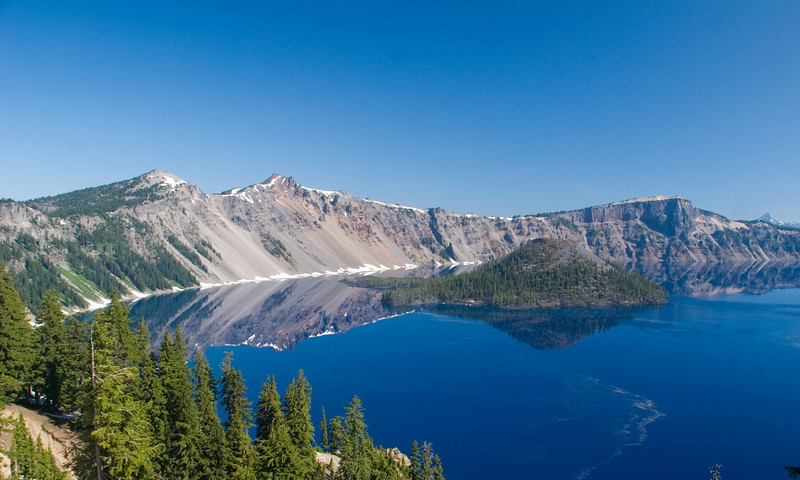 Crater Lake, Oregon. Only in the morning is the water this still. Once the boat tours start, it all changes. The deepest blue lake I've ever seen!