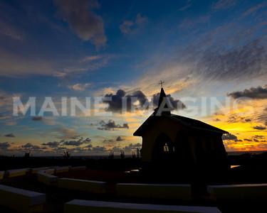 Sunrise silhouettes a small chapel on Aruba.
