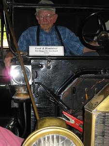 Old man and old car with directive sign