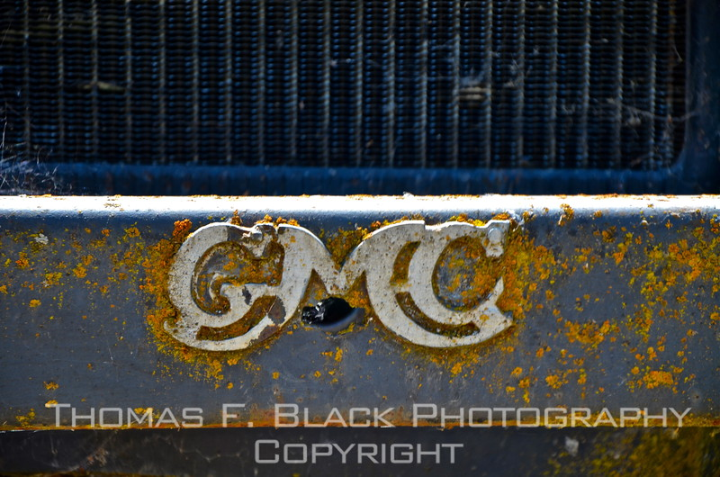 This through frame 103, two different General Motors trucks. These initials appear on front bumper of one.