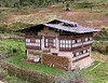 A basic Bhutanese house, showing the three stories, with wood ready for the approaching winter.