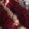 The monks lined up for their meal, ignoring the tourists taking their photos.