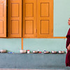 A monk walks by a monastery door, with morning ablution instruments (toothbrushes, toothpaste, combs, etc) lined up along one of the berms
