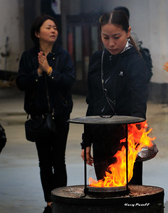 lighting incense at a temple