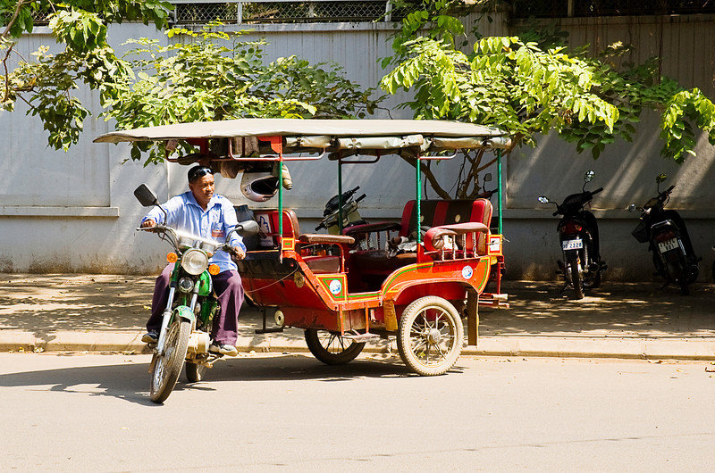The most common taxi in Cambodia was this style of brightly painted, canopied two-wheeled add-on to a motorbike. After work the full bike seat could be re-fitted for family transportation.