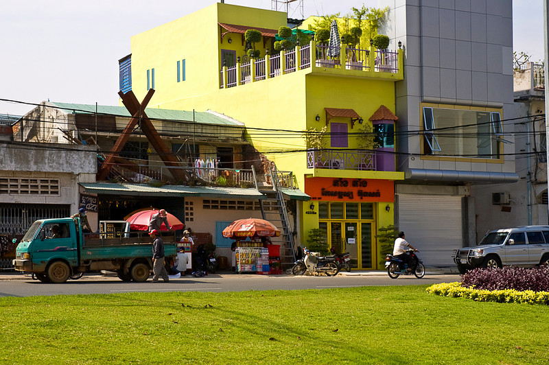 Architectural variations; on the right a modern house with a garage at street level; the yellow building is more typically vernacular Southeast Asian with a shop below and family living quarters above. The other building is apparently an automotive repair shop with at through-the-roof engine hoist compromising the family's second floor patio. The two kiosks sold food and drinks.