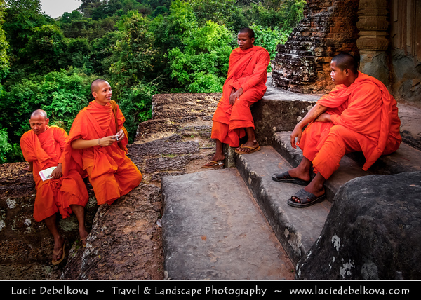 Asia - Cambodia - Prasat Angkor Wat - Largest Khmer temple complex in world - UNESCO World Heritage Site - One of the most important archaeological sites in South-East Asia stretching over some 400 km2 containing magnificent remains of the different capitals of the Khmer Empire from the 9th to the 15th century - Buddhist monks in traditional orange robes wondering the ancient monuments