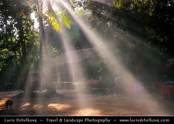 Asia - Cambodia - Prasat Angkor Wat - Largest Khmer temple complex in world - UNESCO World Heritage Site - One of the most important archaeological sites in South-East Asia stretching over some 400 km2 containing magnificent remains of the different capitals of the Khmer Empire from the 9th to the 15th century - Sunrays penetrating the misty forest