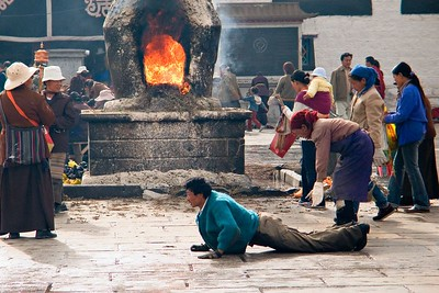 In the foreground a pilgrim travels by prostrating himself, stretching out his arms, marking a line at the end of his fingers, standing up, stepping up to the line, and repeating the process. They go around the temple in this manner all day. They also travel hundreds of kilometers from their home village by serial prostration. Incense is being burned in the oven.