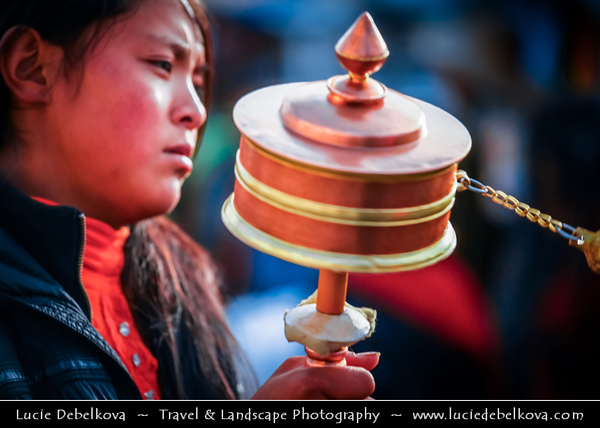 Asia - China - Tibet - Lhasa - Tibetian capital on Tibetan Plateau at altitude of 3,490 metres (11,450 ft) - Barkhor Square - Area of traditional narrow streets around Jokhang Temple, popular devotional circumabulation for pilgrims and locals - Local Tibetian Woman with Small Traditional Tibetan Buddhist Prayer Wheel