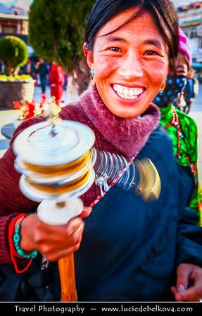 Asia - China - Tibet - Lhasa - Tibetian capital on Tibetan Plateau at altitude of 3,490 metres (11,450 ft) - Barkhor Square - Area of traditional narrow streets around Jokhang Temple, popular devotional circumabulation for pilgrims and locals - Local Tibetian Woman with Small Traditional Tibetan Buddhist Prayer Wheel