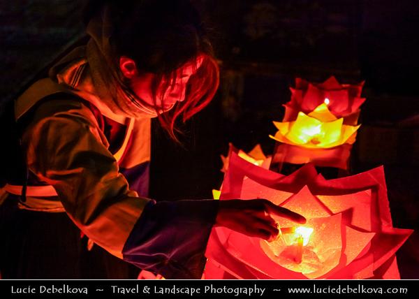 Asia - China - Southwest China - Yunnan Province -  Lijiang - 丽江- Likiang - Old Town - UNESCO Heritage Site - Naxi woman lighting candle lanterns