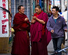 Tibetan monks with cellphone and Chinese shopper passing liquor store, commercial district, Lhasa