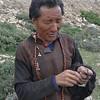 Tibetan man making wool out of yak hair