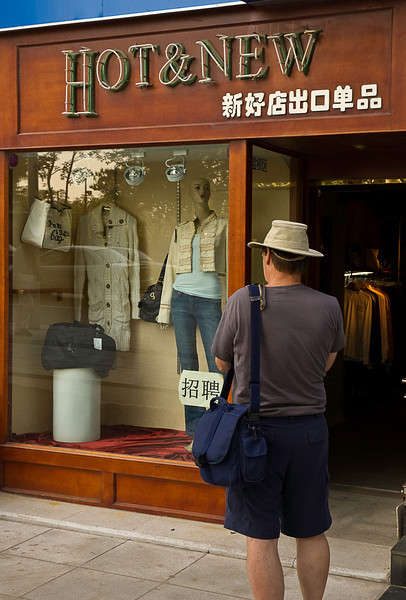 Tourist in need of hot and new clothes finds the right place, downtown, Dalian.