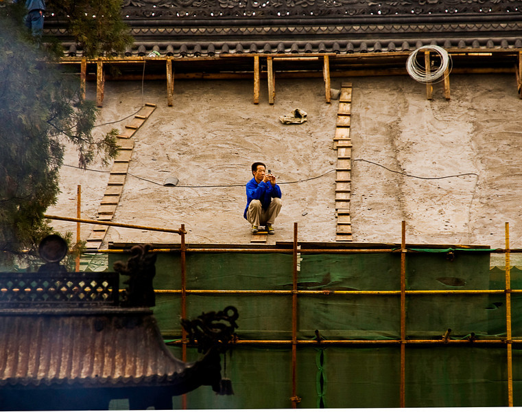 Cellphone photographer taking a break from roof repairs at Da Ci'en Temple; incense burner at lower left, Xian