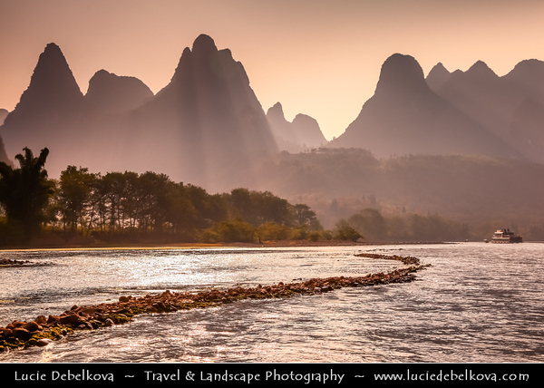 Asia - China - Southern China - Guanxi Province - Guilin - Yangshuo - Famously spectacular limestone karst along Li river surrounded by coutless verdant limestone hills, peaks & towers - Beautiful soft sunset light
