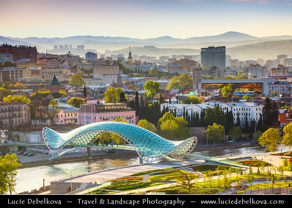 Georgia - Tbilisi - თბილისი - Capital City - City Skyline & Bridge of Peace - Tbilisi's ultra-modern pedestrian walkway - Fascinating structure of glass and iron - Connects the ancient city of Tbilisi—now a growing suburb of cafes, restaurants, tourist shops & art galleries to new district (to-be-developed) across Mt'k'vari River