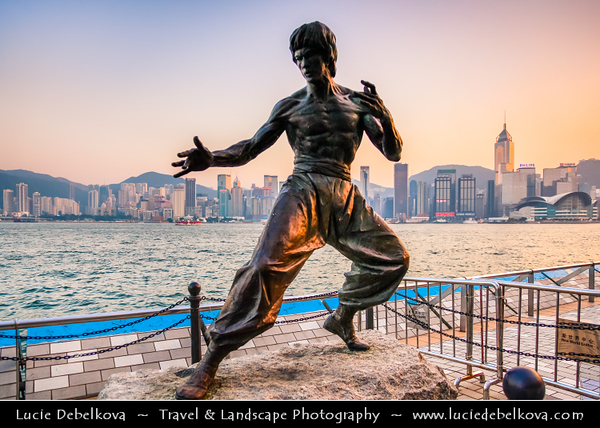 Asia - Hong Kong - 香港 - Special administrative regions (SARs) of the People's Republic of China - View of high rise buildings, skyscrapers on the city skyline of Victoria Harbour in Central district of Hong Kong Island & Kung Fu film star Bruce Lee statue on the Avenue of Stars waterfront promenade during Sunset