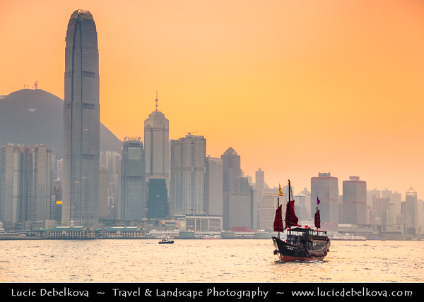 Asia - Hong Kong - 香港 - Special administrative regions (SARs) of the People's Republic of China - View of high rise buildings, skyscrapers on the city skyline of Victoria Harbour in Central district of Hong Kong Island & Traditional Chinese Junk boat with Red Sail - Sunset