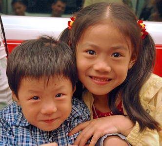 A couple of cute children pose for 'Uncle' while riding the Kowloon-Canton Railway. Many children call adults 'Uncle' or 'Auntie' as a sign of respect.