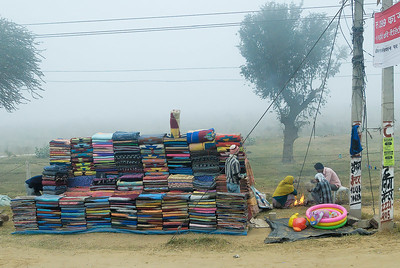 Across the road from the gas station rug sellers warm themselves aound a fire. The mornings were chilly and foggy.
