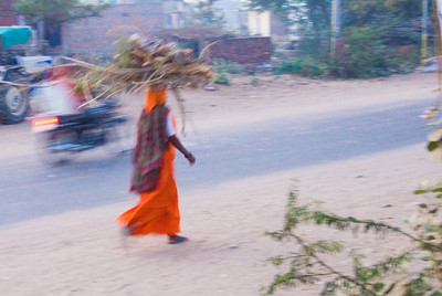 A local hurries home with a load of firewood