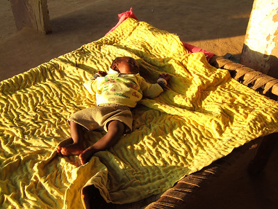 A baby in the village snoozes in the evening sun
