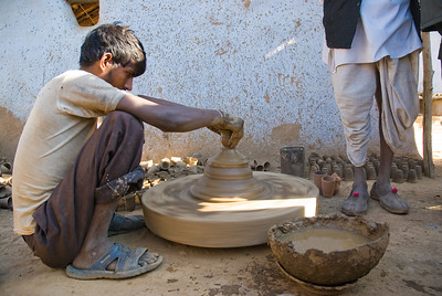 The village potter. The wheel was spun manually. The little cups in the background are used for tea, and broken when used once