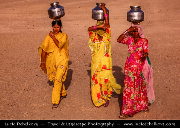 """India - Rajasthan - Jaisalmer - """"Golden City of India"""" - Former medieval trading center in heart of Thar Desert - Daily life with women in traditional dress carrying water on their head"""